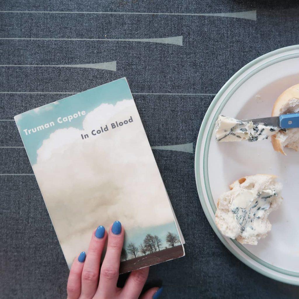 Livre De sang froid de Truman Capote et assiette avec du pain et du fromage bleu